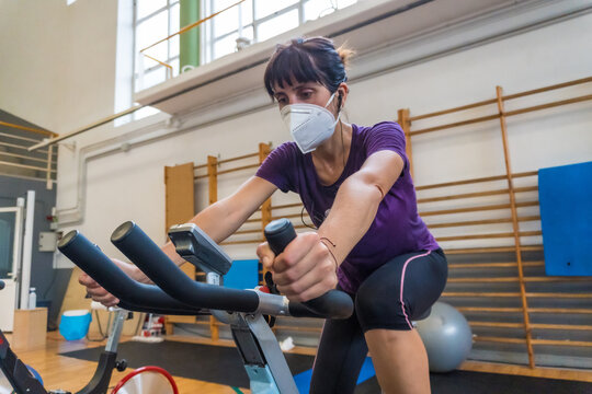 Young caucasian girl with a face mask on a stationary bike in an empty gym due to the low capacity in the new normal, social distance, covi-19, coronavirus