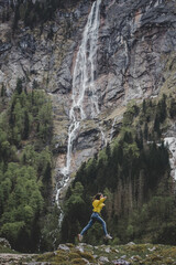 Young brunette girl in yellow sweatshirt jumps on background of Rothbach waterfall, pine forest & rock mountain cliff. Schonau am Konigssee. Bavaria. Germany