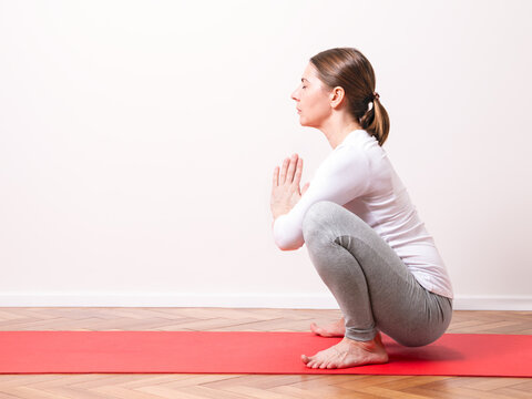 Middle aged white woman practices yoga in Malasana frog pose profile view on white background.