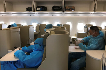 Vietnamese nationals wearing protective suits are seen onboard before a repatriation flight from Singapore to Vietnam amid spread of the coronavirus disease (COVID-19) outbreak at Changi airport, Singapore