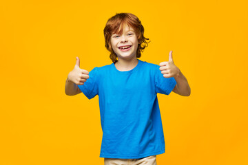 joyful child in a blue t-shirt is showing a thumb and having fun