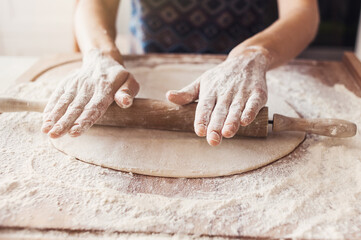 Woman baking bread or pizza dough with rolling pin on wooden table