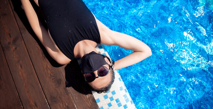 Woman in black protective mask from coronavirus bathes in hotel pool, summer epidemic vacation. Social distance concept