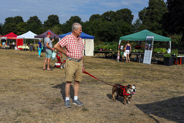 A man stands with his dog on a hot day at a farmers market in Ripley