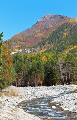 Beautiful autumn landscape with a fast mountain river in the foothill valley and the Eastern Sayan Mountains. Baikal region, Buryatia, Tunka valley, Arshan village. Natural autumn background