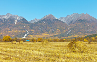 A beautiful autumn landscape with a harvested grain field in the foothill valley and the Eastern Sayan mountain range. Baikal region, Buryatia, Tunka valley. Natural autumn rural background