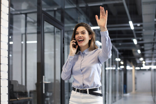 Attractive business woman talking by smartphone and waving hand by greeting you.