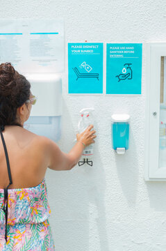 Coronavirus safety measures in the pool: woman using a bottle of hand sanitizer to clean sunbed and hands. Summer with covid 19 and new normal.