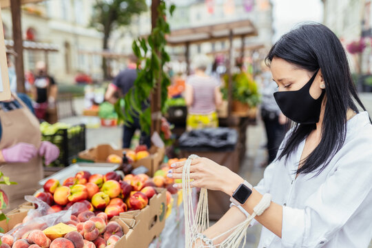 Portrait of pretty house wife in protective mask holding net bag and buying organic products at farmers market during coronavirus. New social rules after pandemic.