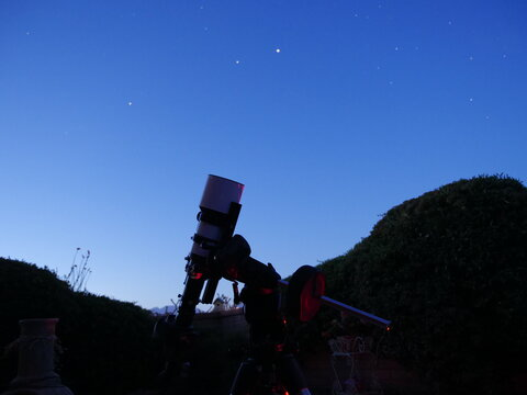 An amateur astronomy telescope set up in a back yard
