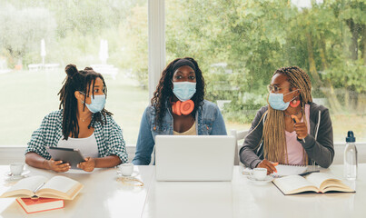Three African American girls students sitting at the table preparing for exam or making homework together, they are using lap top and digital tablet wearing surgical masks. Back to school concept.