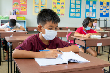 Elementary school wear mask for protect corona virus are studying at desks In...