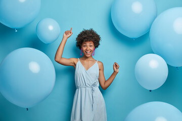 Upbeat cheerful festive woman with hollywood smile, laughs out of joy, moves carefree and dances to music, has fun, makes happy holiday photo, celebrates anniversary, surrounded by balloons.