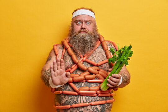 Serious motivated overweight man makes stop gesture, keeps to strict vegetarian diet and chooses celery to eat, wears sport headband, stands naked, wrapped by sausages, stands indoor. Junk food