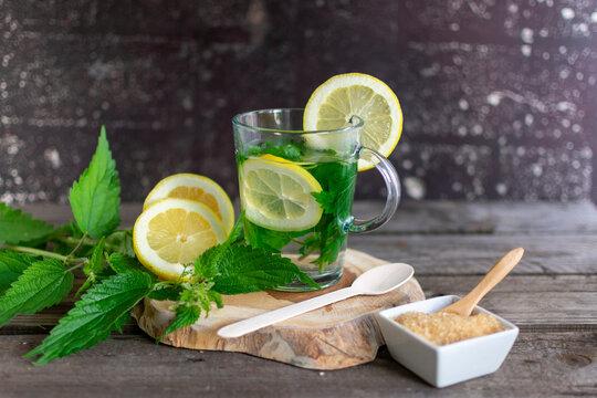 frische Brennessel mit Zitrone auf einem Holzbrettchen mit braunem Zucker für einen Tee