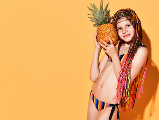 Lovely schoolgirl with cute african braids posing in striped bikini holding big pineapple close to...