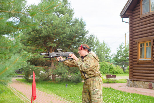 Girl playing in lasertag shooting game, girl with a gun, war simulation.