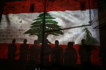 Christian worshippers stand by a wall as a Lebanese national flag is projected on it in solidarity with the Lebanese people following the blast in Beirut, outside a church in Nazareth