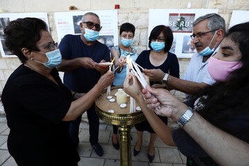 Christian worshippers light candles to express their condolences to the Lebanese people following the blast in Beirut, outside a church in Nazareth