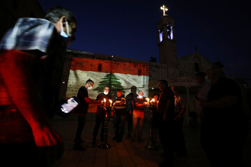Christian worshippers light candles to express their condolences to the Lebanese people as a Lebanese national flag is projected on a wall outside a church following the blast in Beirut, in Nazareth