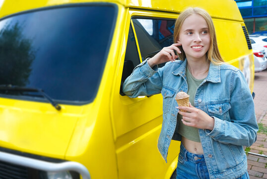 Beautiful Young caucasian Lady eat Ice Cream in front of ice cream van. Woman standing with ice-cream before an yellow old hippie bus.