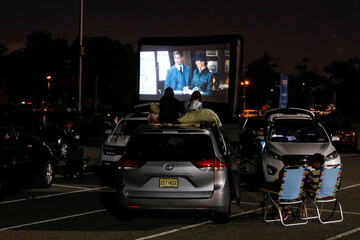 People attend a pop-up drive-in theater in the parking lot of Citi Field in Queens, New York