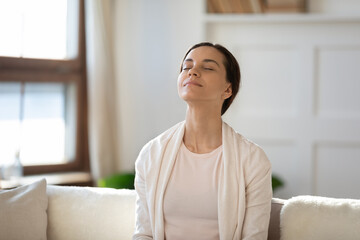 Mindful young woman breathing fresh air with closed eyes, sitting on sofa alone indoors. Peaceful...