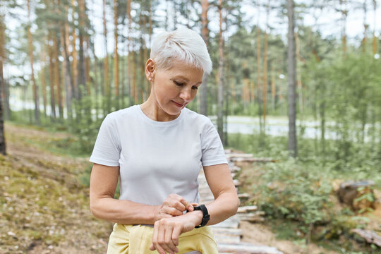 Active mature woman with short blonde hair posing outdoors, getting ready for jogging exercise, setting smart watch, tracking heart rate and pulse. People, sports, fitness and technology concept