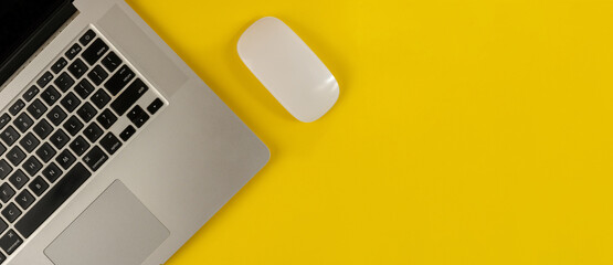 Top view of laptop and mouse on yellow background