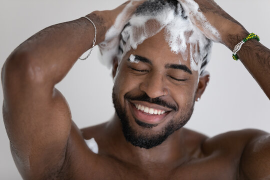 Close up smiling African American handsome young man washing cleaning hair with foamy anti-dandruff shampoo, taking shower, enjoying morning routine procedure, standing in bathroom