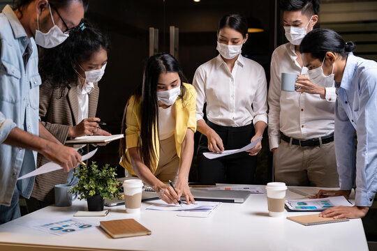 Working late night of Interracial business team wear face mask brainstorm at new normal office