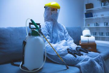 Person with toilet paper stock and protective antiviral mask, suit, helmet and chemical decontamination sprayer bottle in home isolation.