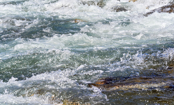 Rapid spring river flowing over rocks on sunny day, forming white water waves, closeup detail - abstract nature background
