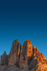 Beautiful sunset in magical Three Dolomite peaks at the national park Three Peaks (Tre Cime, Drei Zinnen) in Autumn colors at blue deep sky, South Tyrol, Italy, details