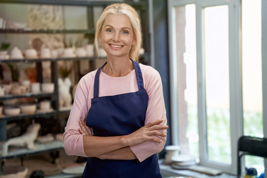 Successful business owner. Portrait of beautiful happy craft woman wearing apron looking at camera and smiling while standing in her art studio or craft pottery shop