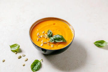 Bowl of pumpkin or carrot vegetarian cream soup decorated by fresh basil, olive oil and pumpkin seeds on white texture table with ingredients above.