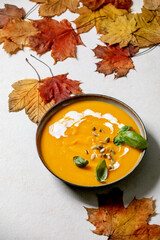 Bowl of pumpkin or carrot vegetarian cream soup decorated by fresh basil, cream and pumpkin seeds on white texture background with yellow autumn maple leaves above.
