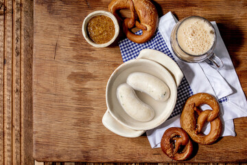 Munich Bavarian traditional white sausages in ceramic pan served with german sweet mustard, mug of dark beer and pretzels bread on white and blue napkin over wooden background. Flat lay, space.