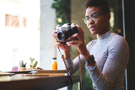 Attractive afro american photographer making pictures of cafe interior earning money using creative ideas,young casually dressed female black model pending time on hobby taking photo on vintage camera