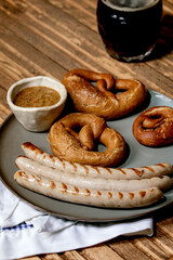 Bavarian traditional grilled pork sausages on ceramic plate served with german sweet mustard, mug of dark beer and pretzels bread on white and blue napkin over wooden background.