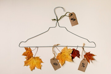 Autumn sale concept. Wire hanger, labels with percents, yellow autumn leaves over beige background. Flat lay.