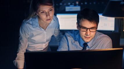 Portrait of Businessman Uses Desktop Computer, His Female Project Manager Explains Specific Tasks,...