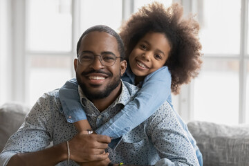 Portrait of cute little ethnic girl hug smiling african American young father show love and affection, happy biracial dad and small daughter hug cuddle, enjoy tender close family weekend together