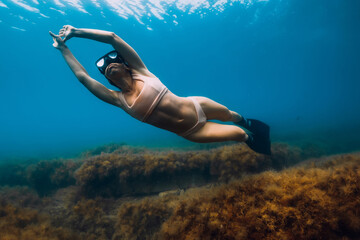 Sporty woman freediver with fins glides underwater in sea. Freediving in ocean