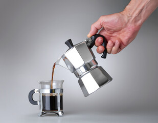 Man's hand holding and pouring italian coffee into a Glass cup