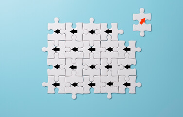 Red arrow print screen on white jigsaw puzzle  move out and chang direction from black arrows. It is business disruption and different thinking idea concept.