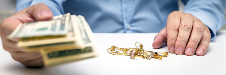 Buying gold jewelry, us dollars and hand of a businessman, panorama