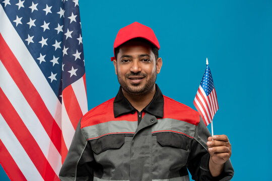 Happy young worker or repairman of Hispanic ethnicity holding small flag