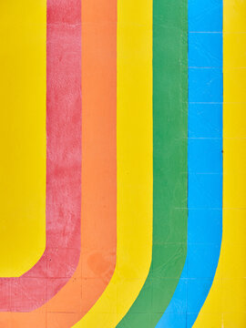 Vertical pattern of curved rainbow painted on a background of an old damaged tile wall
