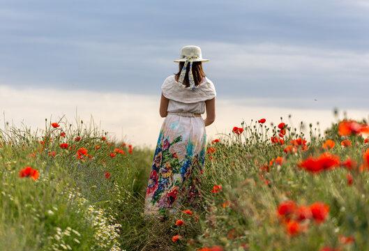 Woman in a white dress posing in a poppy garden